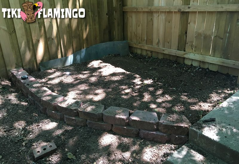 Recycled wall pavers set down to outline a budget DIY patio that will be made from recycled brick.