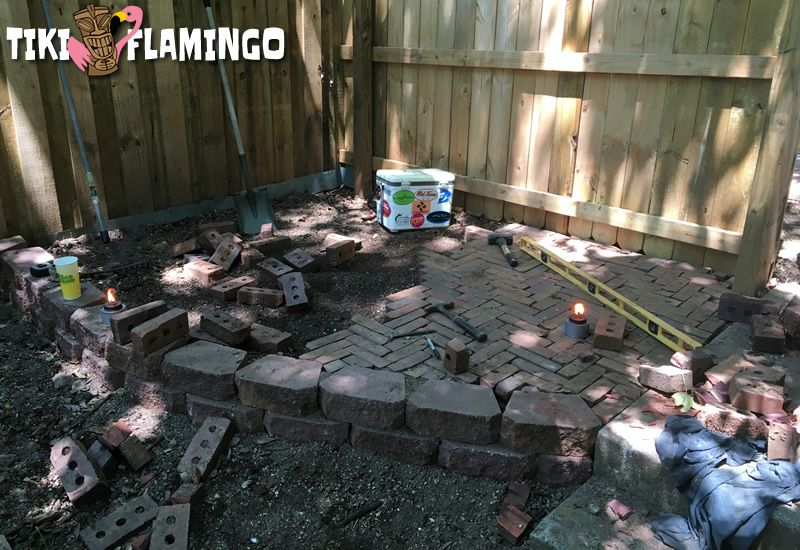 Laying recycled brick in a herringbone pattern to create a beautiful budget patio.